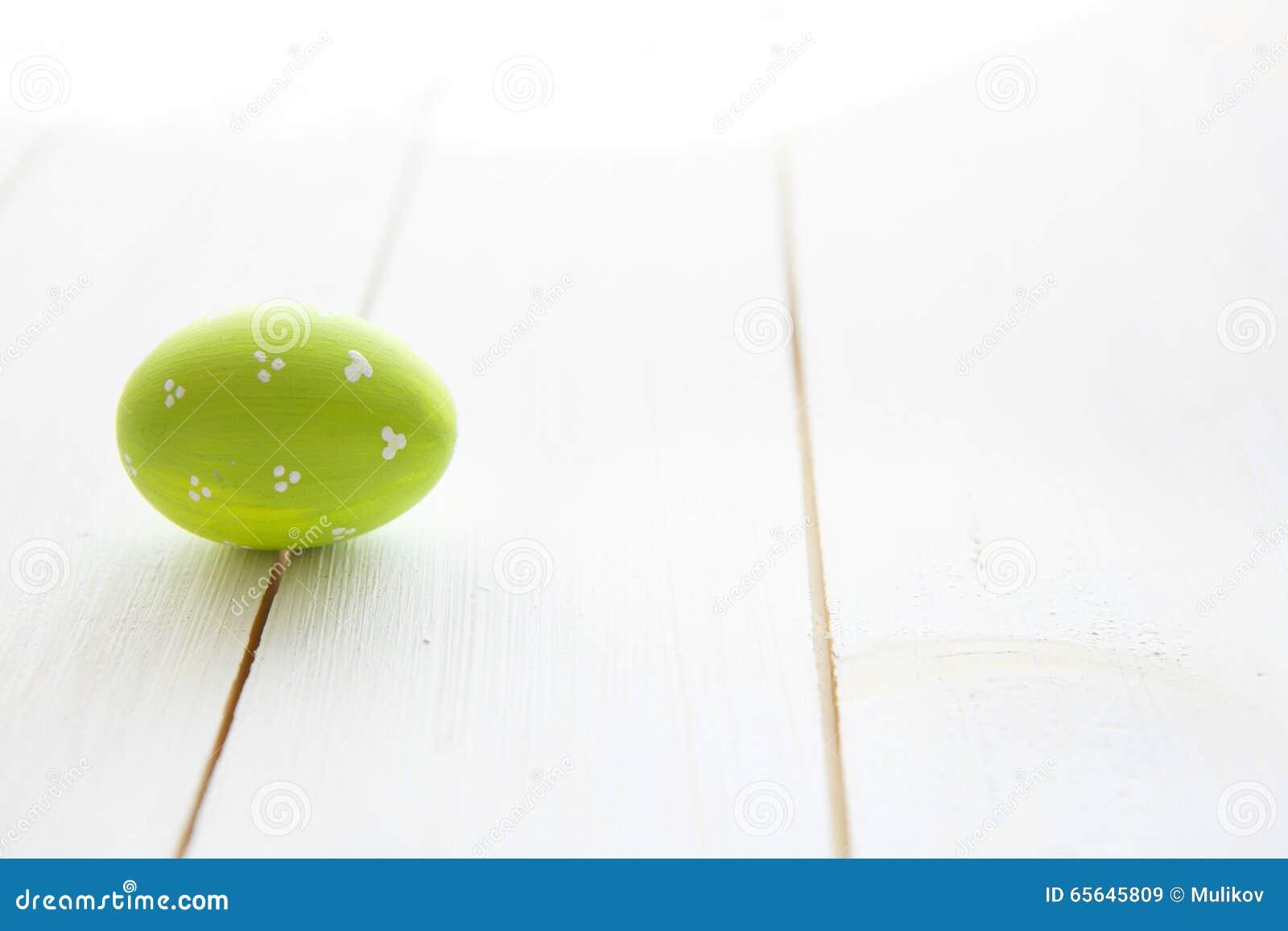 Oeuf vert sur une vieille table en bois blanche