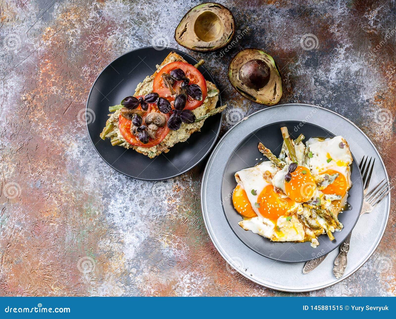 Oeufs au plat avec l asperge, le sandwich avec le pesto, les tomates et les champignons, avocat mûr Vue sup?rieure de petit d?jeu