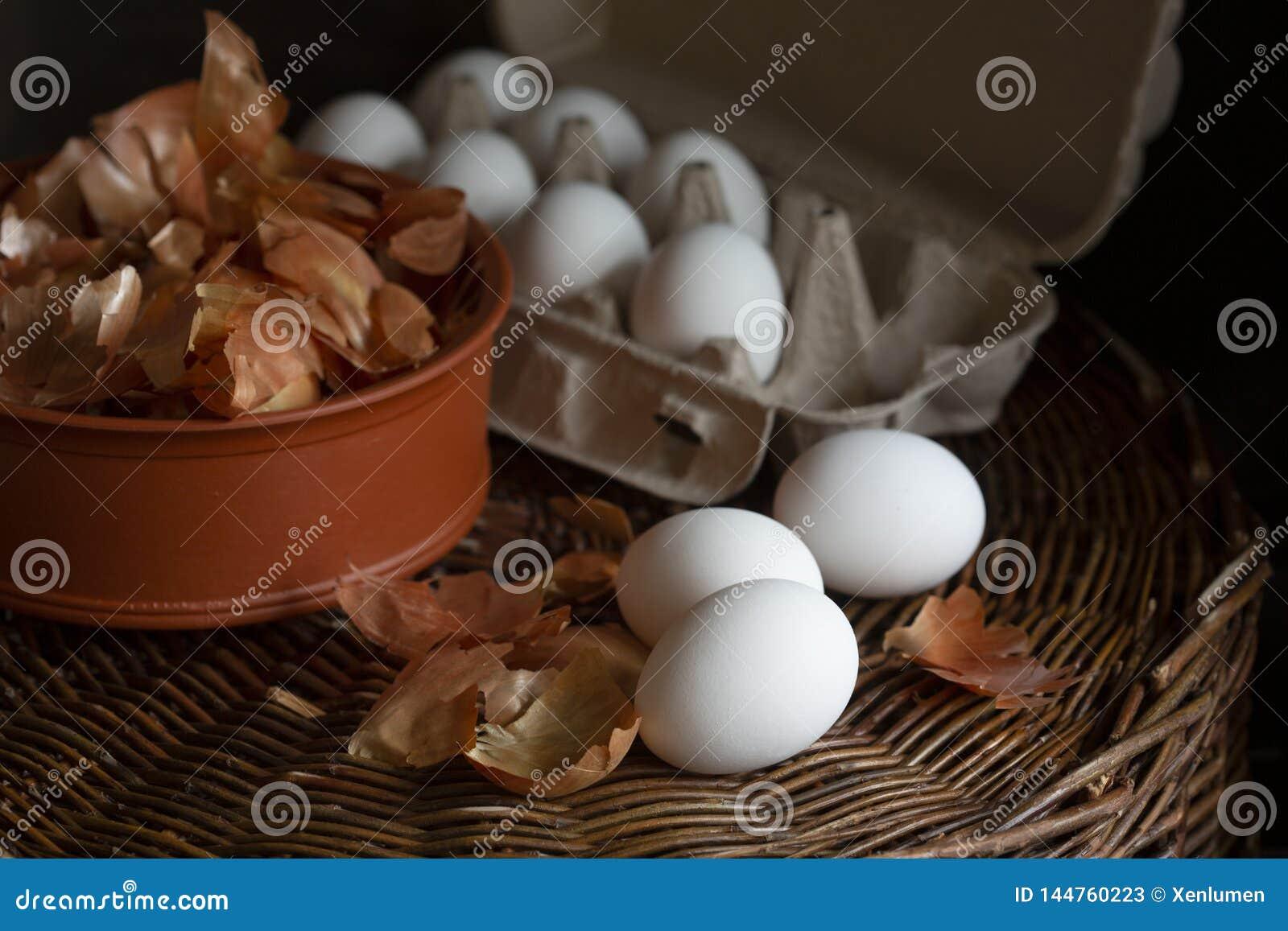 Oeufs blancs dans une boîte avec une peau jaune d oignon dans un plat sur un plateau en osier préparé pour colorer en colorant