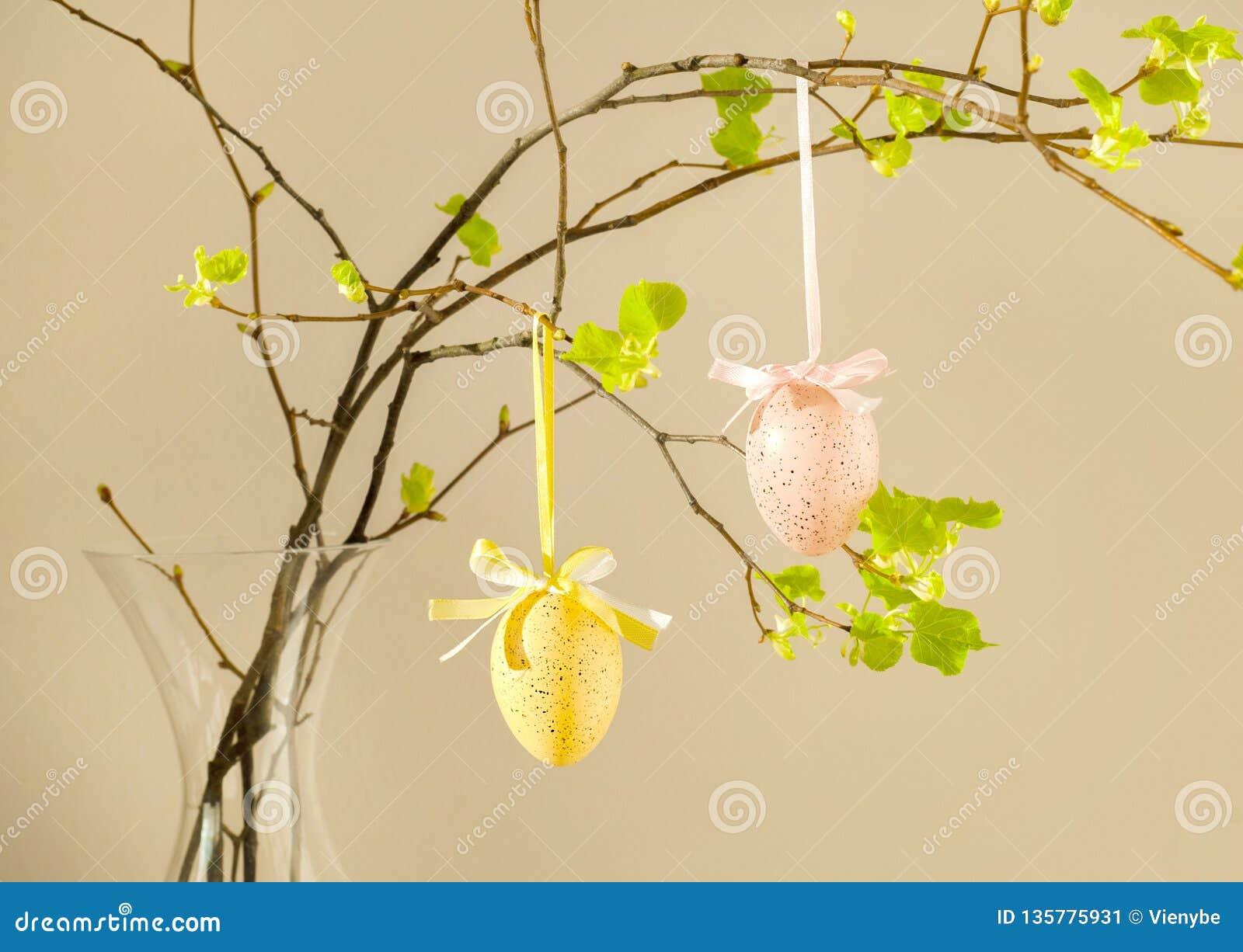 Oeufs colorés avec les feuilles fraîches sur le fond rose Pâques, vacances de ressort