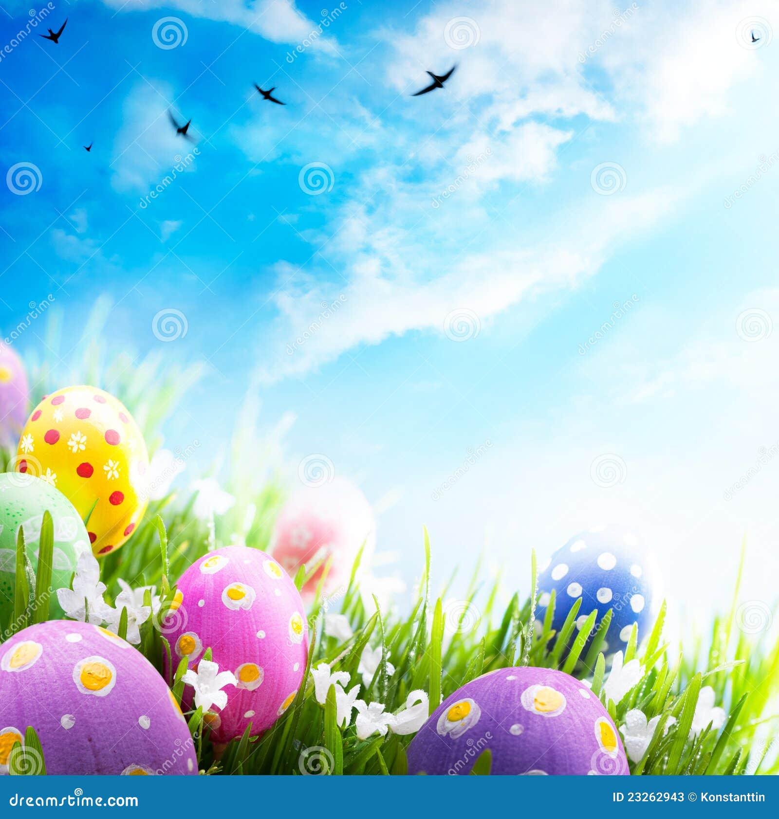 Oeufs de pâques avec des fleurs dans l herbe sur le ciel bleu