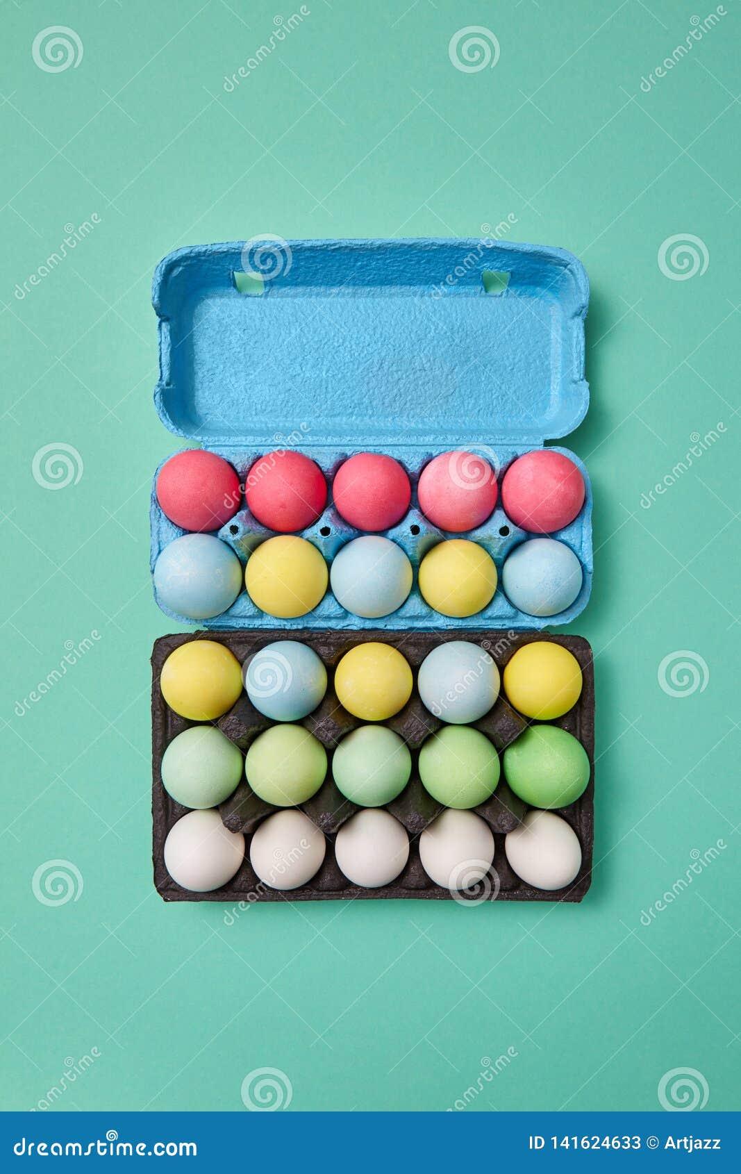 Oeufs de pâques lumineux multicolores dans une boîte en carton bleue et noire sur un fond vert avec l espace de copie Disposition