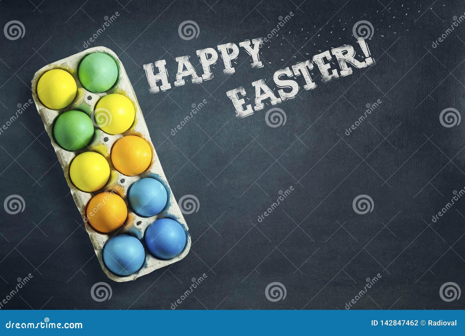 Oeufs de pâques multicolores dans un plateau sur un fond bleu-foncé L inscription dans la craie, Joyeuses Pâques Copiez l espace