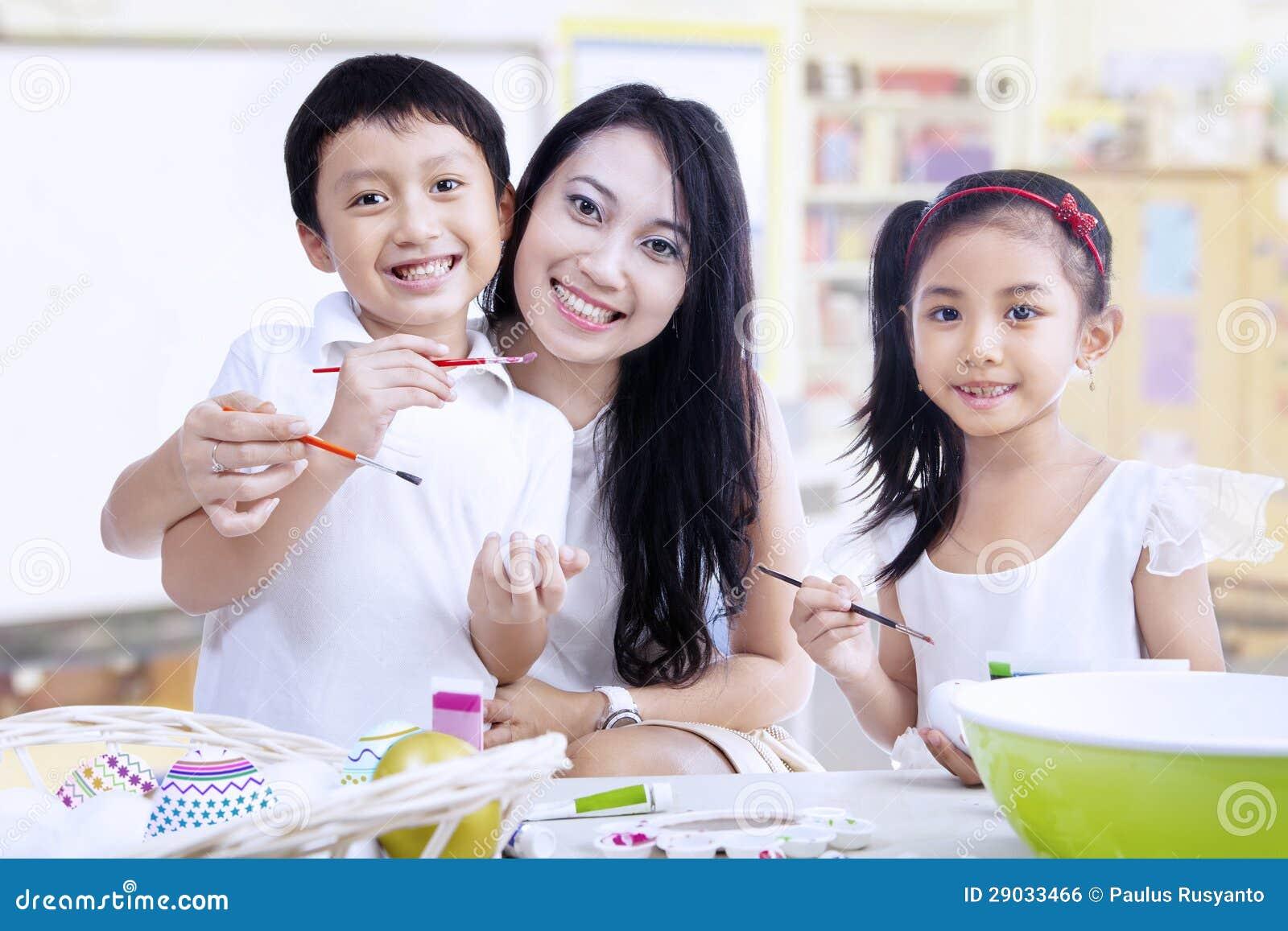 Oeufs de peinture de famille dans la classe