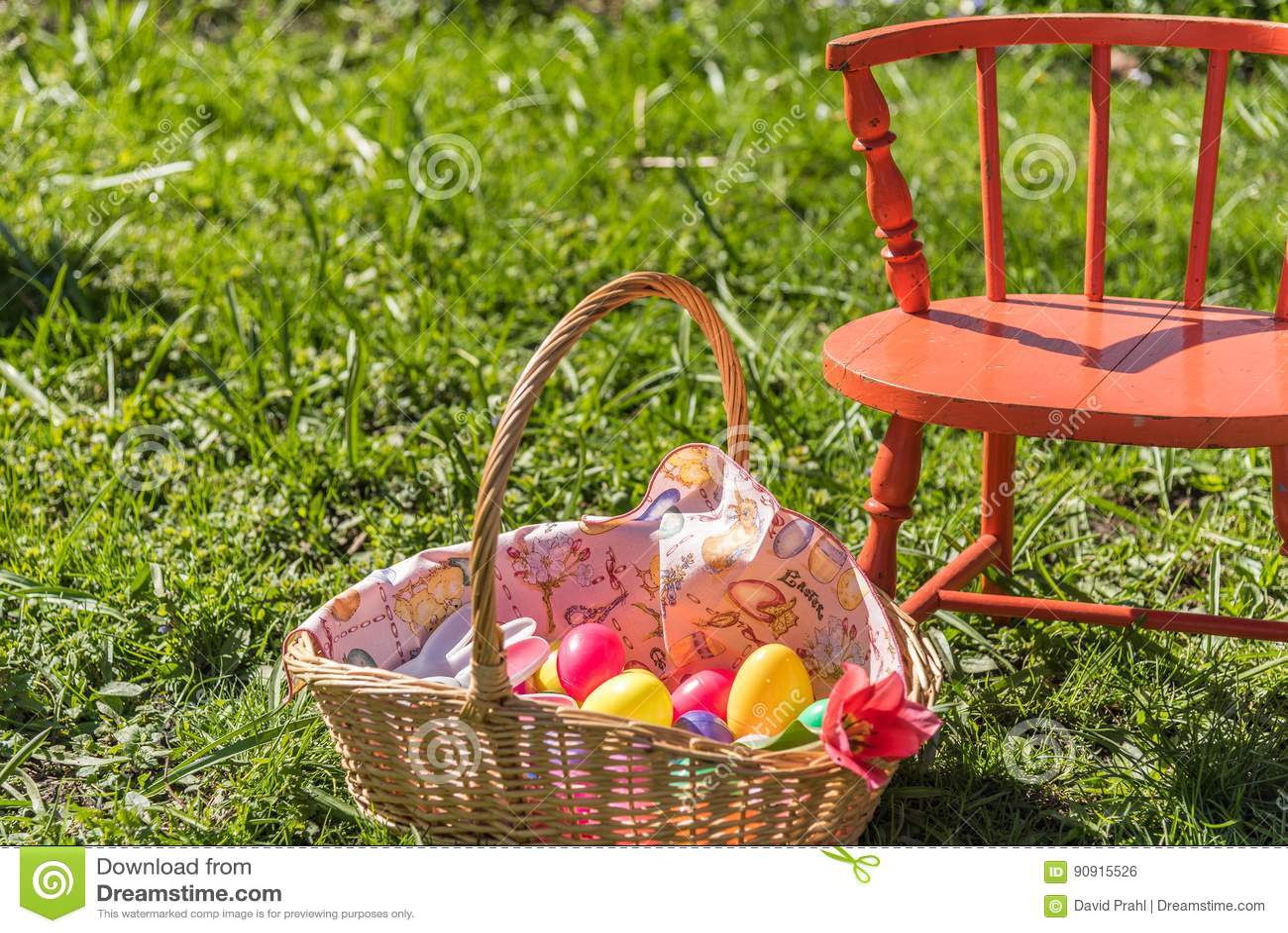 Oeufs en plastique dans le panier de Pâques s étendant dans l herbe verte grande avec la chaise orange
