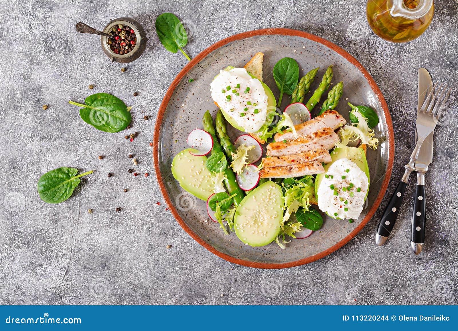 Oeufs pochés sur le pain grillé avec l avocat, l asperge et le filet de poulet sur le gril
