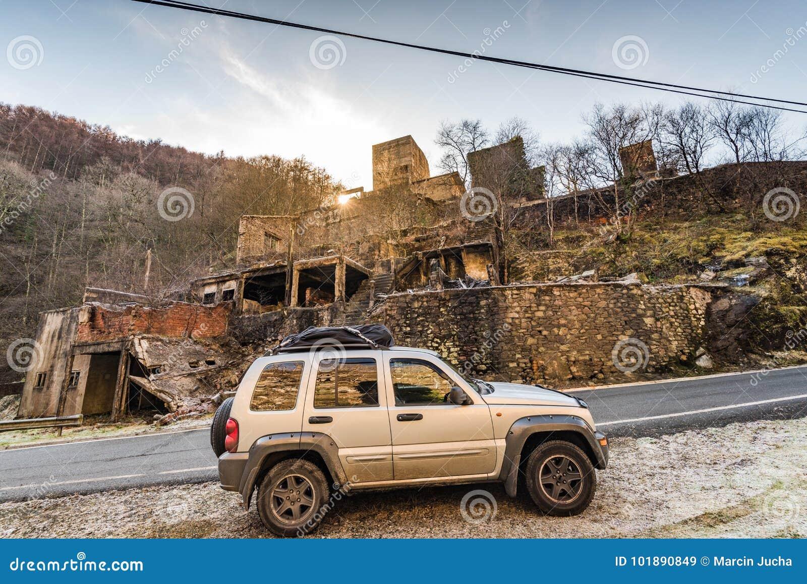Off road car by abandoned burnt village
