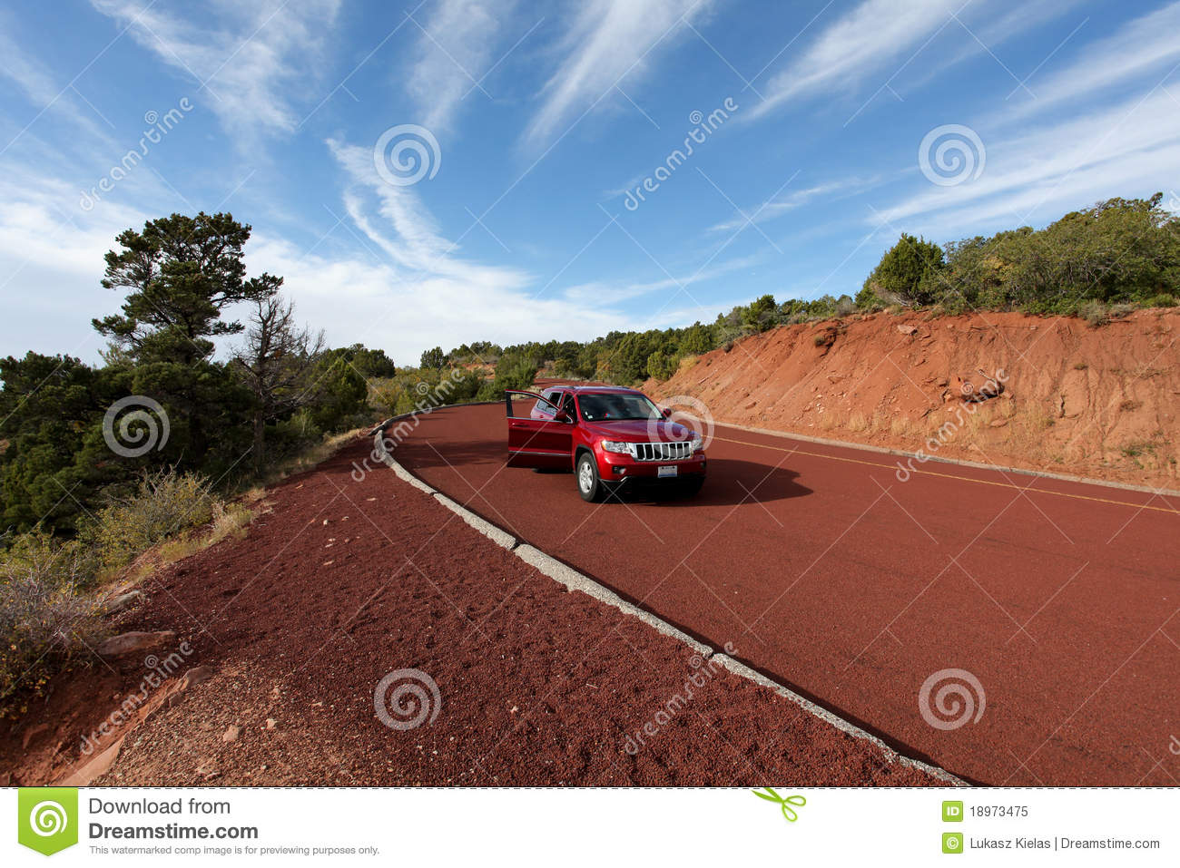 Off road car on red tarmac in high mountains