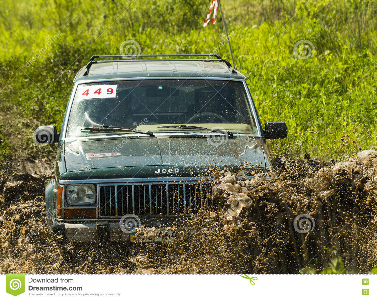 Off-road vehicle brand Jeep Cherokee overcomes a pit of mud
