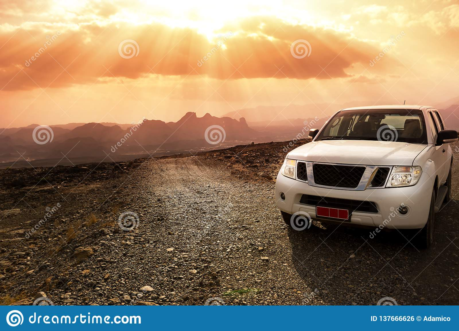 Off-road vehicle on the Jebel Shams mountains and cloudy sky with amazing sunrays