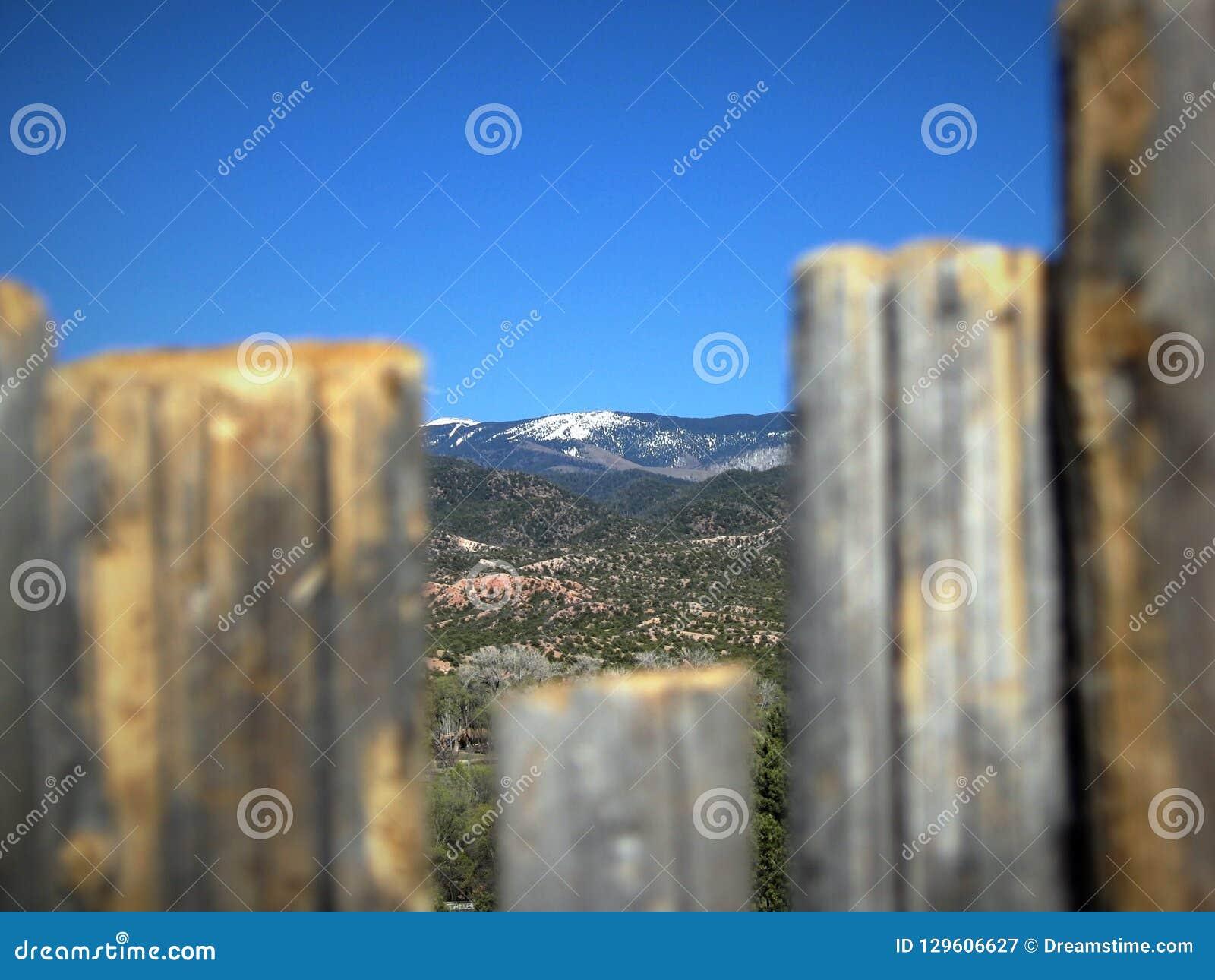 Santa Fe ski basin, the Southern tip of the Sangre de Cristo Mountains, visible through a fence