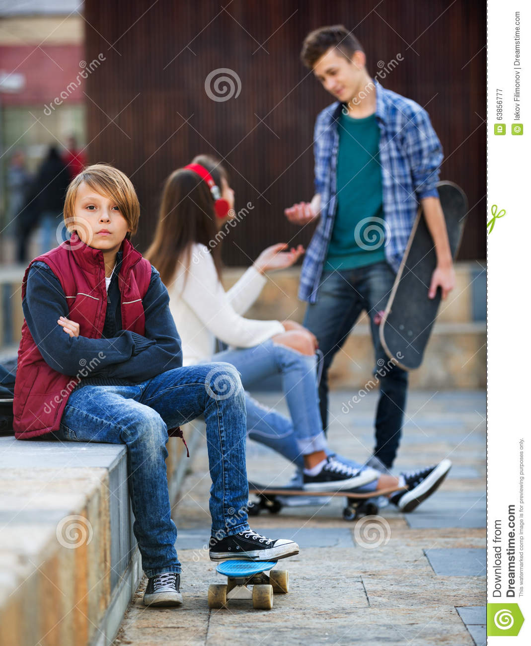 Offended boy and couple of teens apart