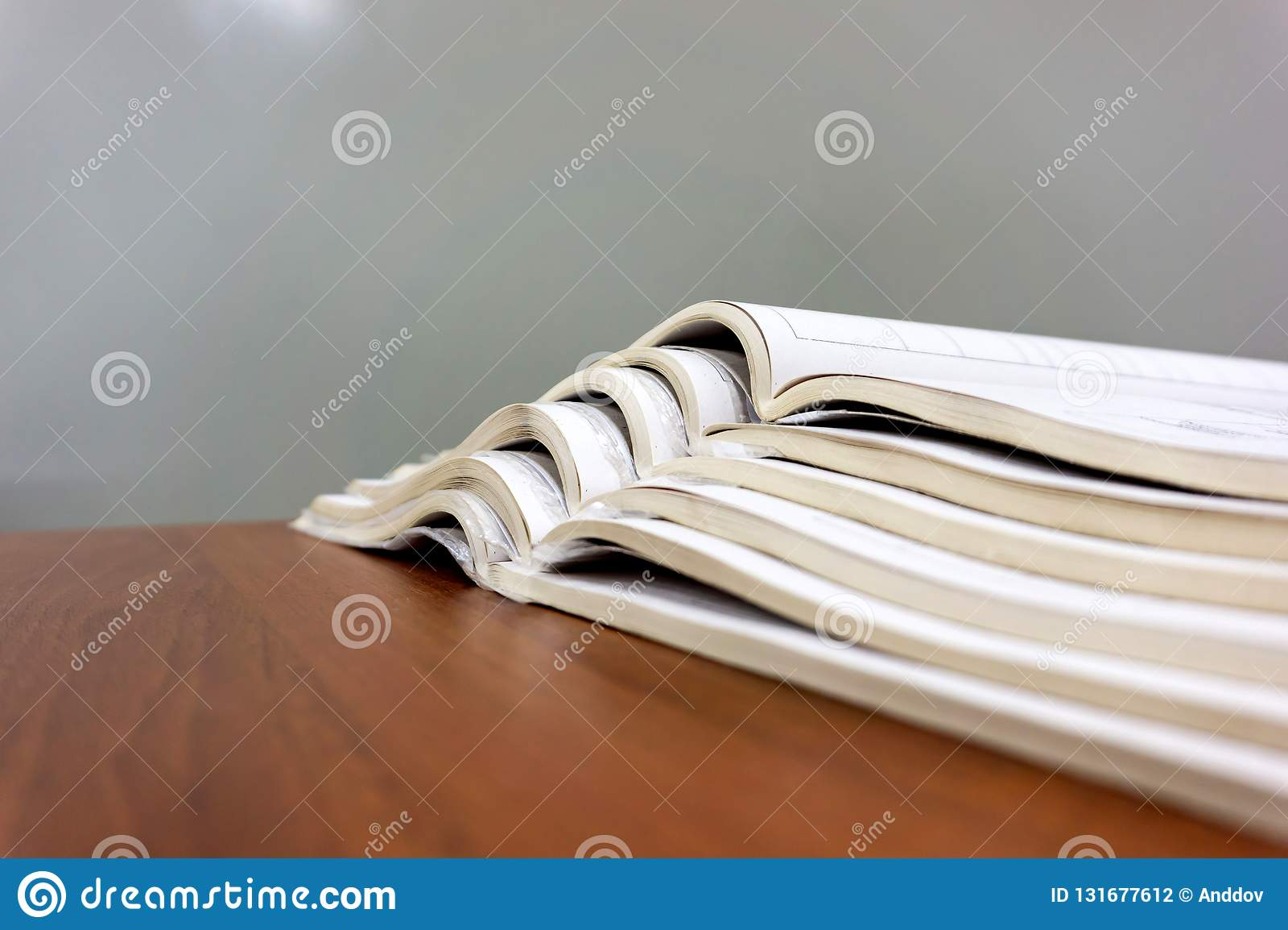 Offene Zeitschriften liegen auf einander auf einer braunen Tabelle, Dokumente sind Staplungsnahaufnahme