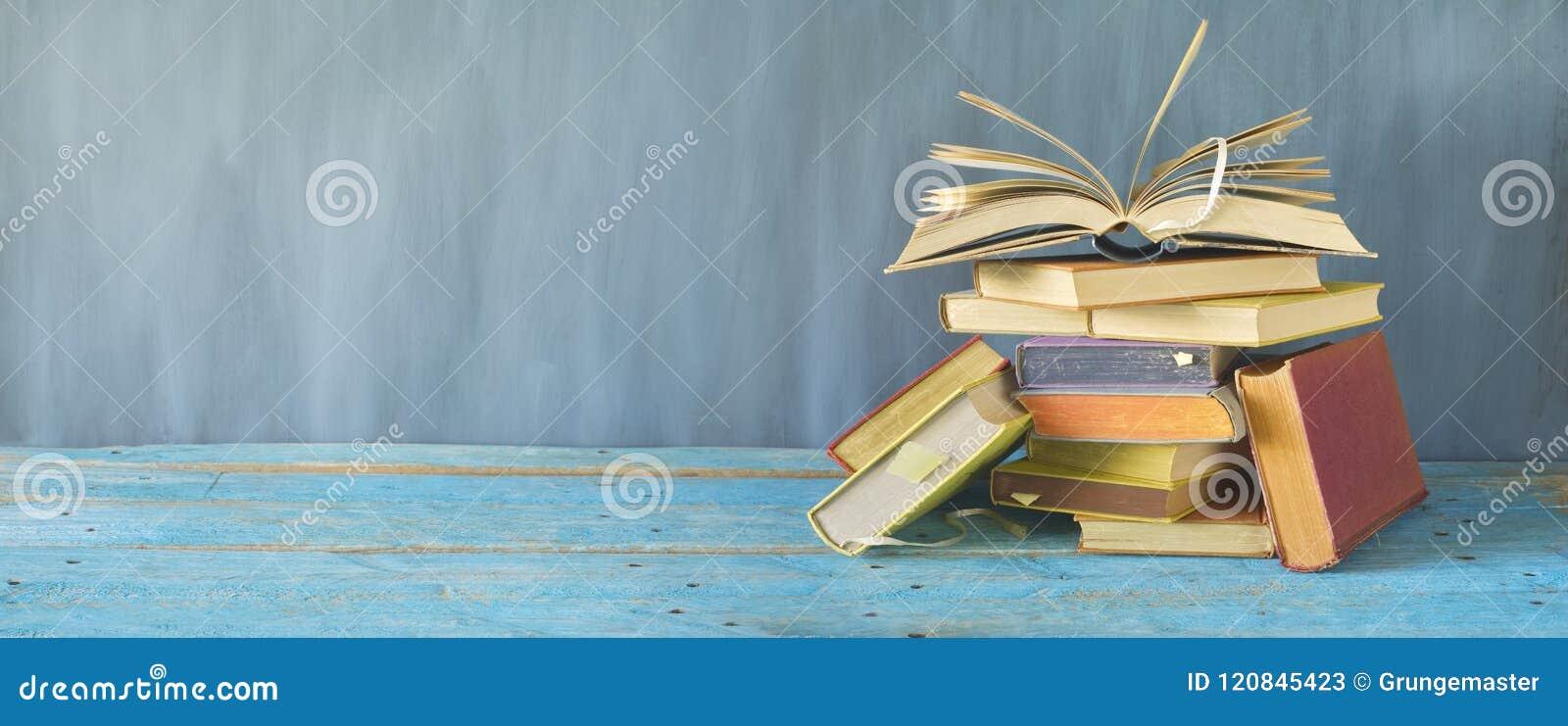 Offenes Buch auf einem Stapel von alten Büchern, Panorama