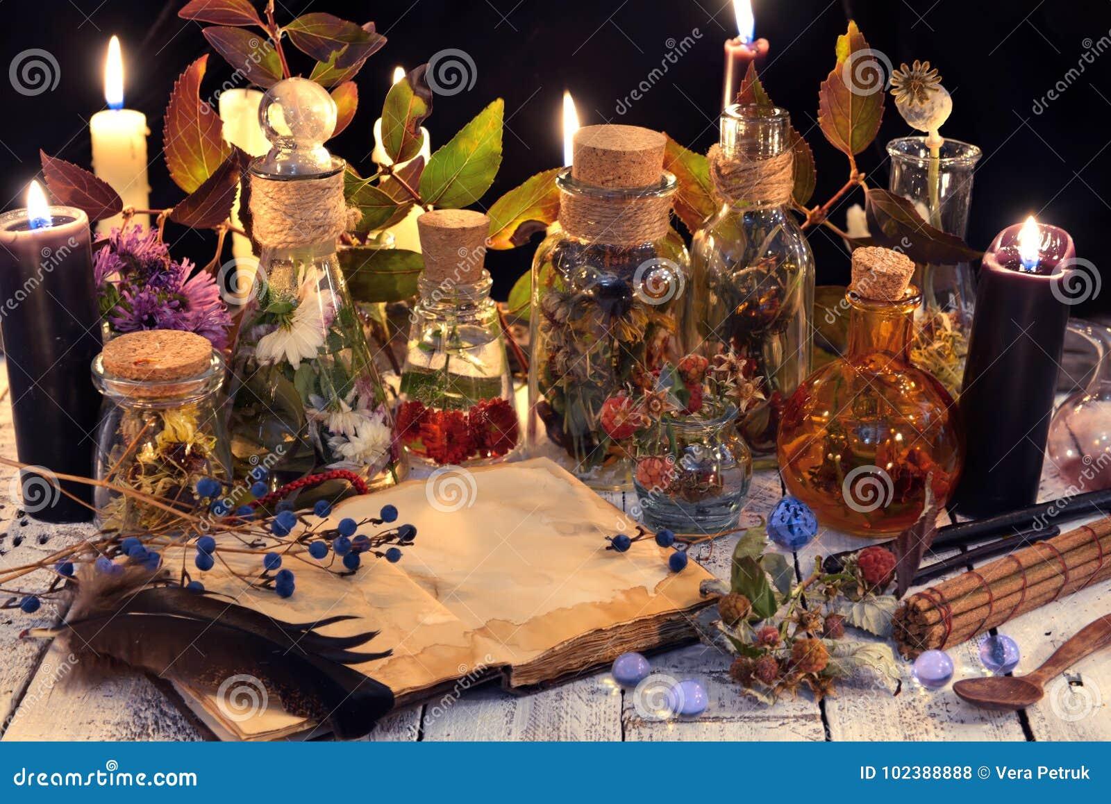 Offenes Buch mit Kopienraum, Kräuter und Beeren, schwarze Kerze und magische Gegenstände auf Hexentabelle