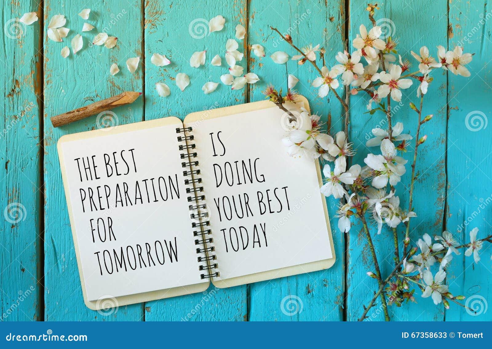 Offenes Notizbuch über Holztisch mit Motivsprechen die beste Vorbereitung für Morgen tut Ihr Bestes heute