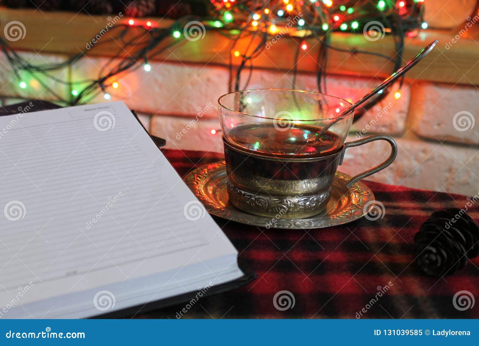 Offenes Tagebuch, transparente Tasse Tee in einem Stahlbecherhalter auf dem Hintergrund eines brennenden Kamins und der Weihnacht