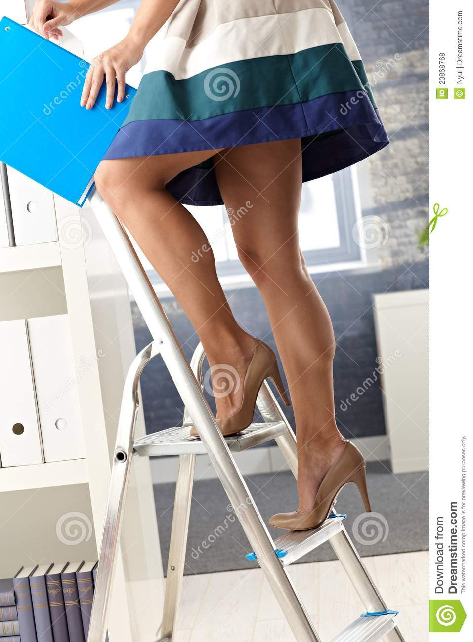Pretty office assistant in short skirt standing on ladder, organizing ...
