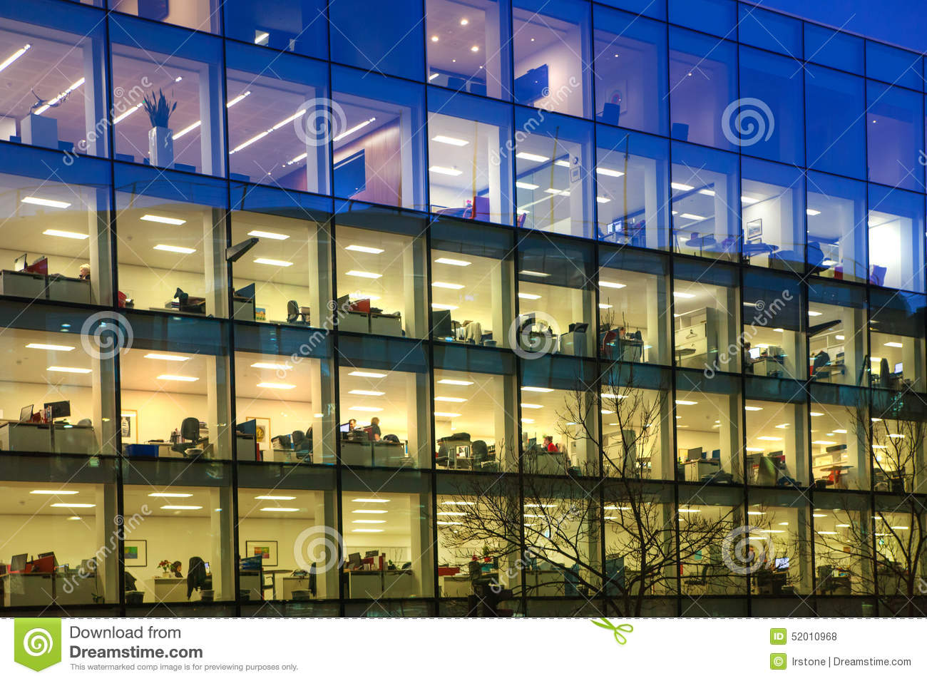 Office block with lots of lit up windows and late office workers inside. City of London business aria in dusk.