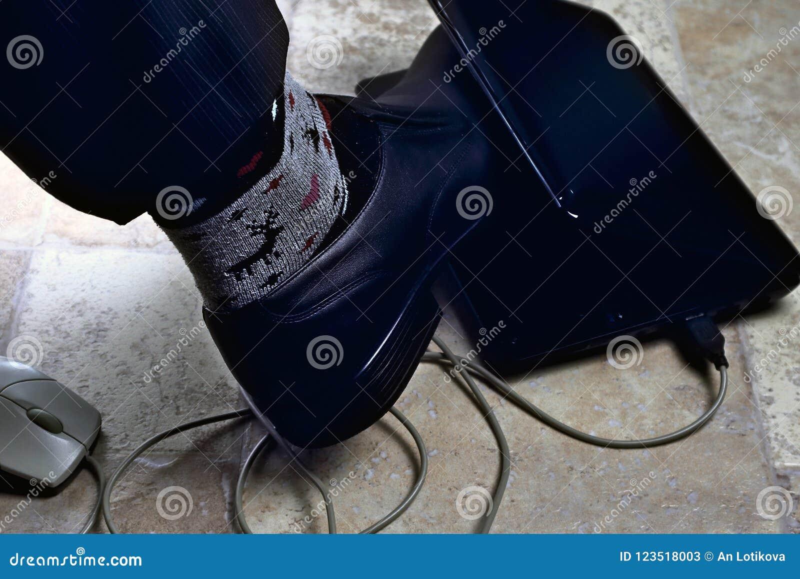 Office clerk`s foot is clamped in netbook as in trap, overwork, work seven days a week