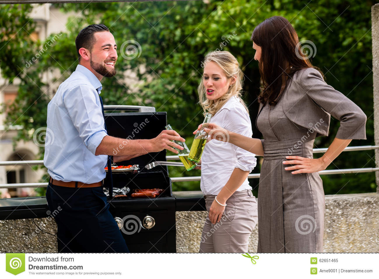 Office Colleagues Grilling Sausages At Bbq After Work Stock Image