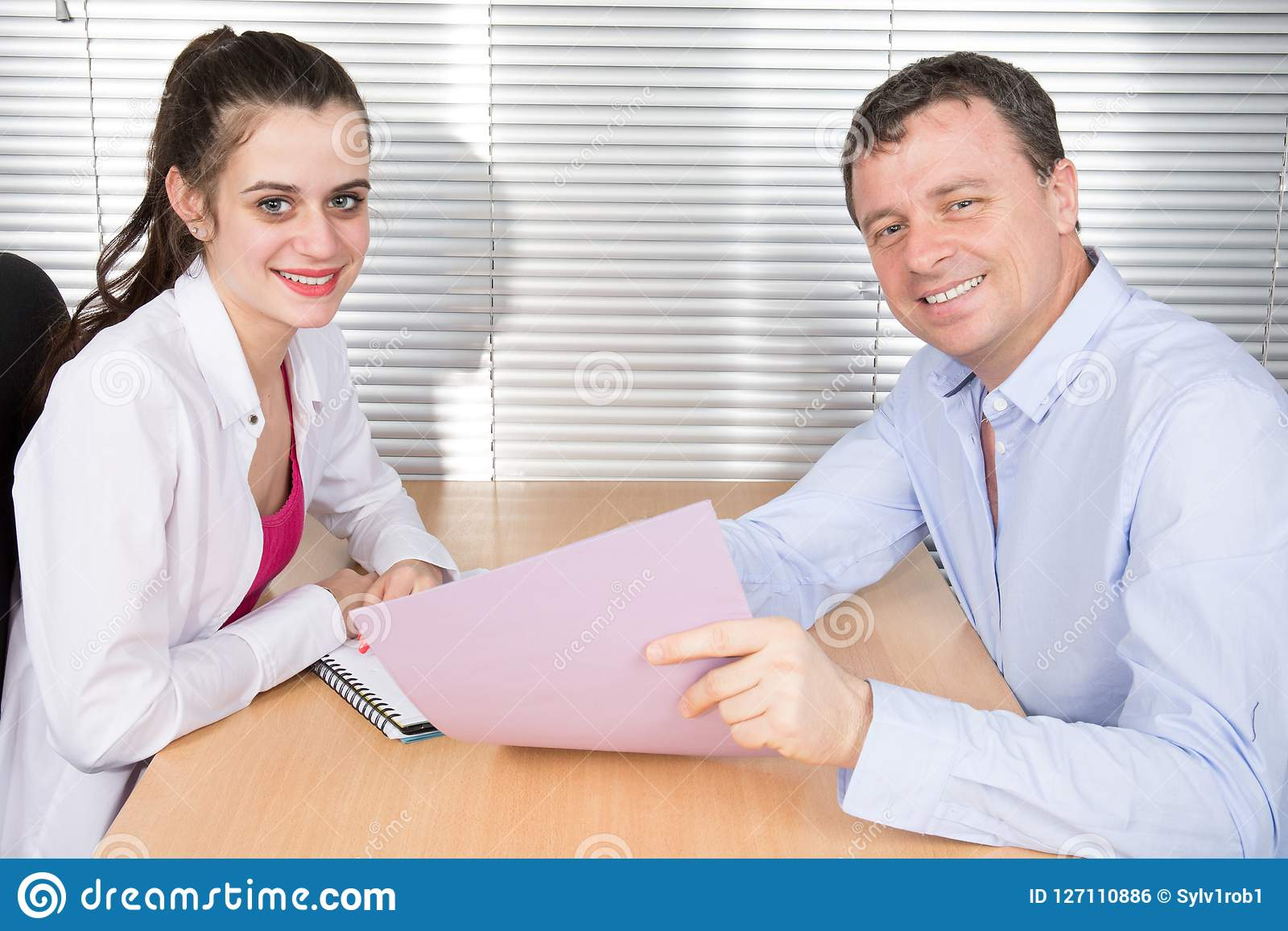 Office colleagues together look at a working folder at office desk