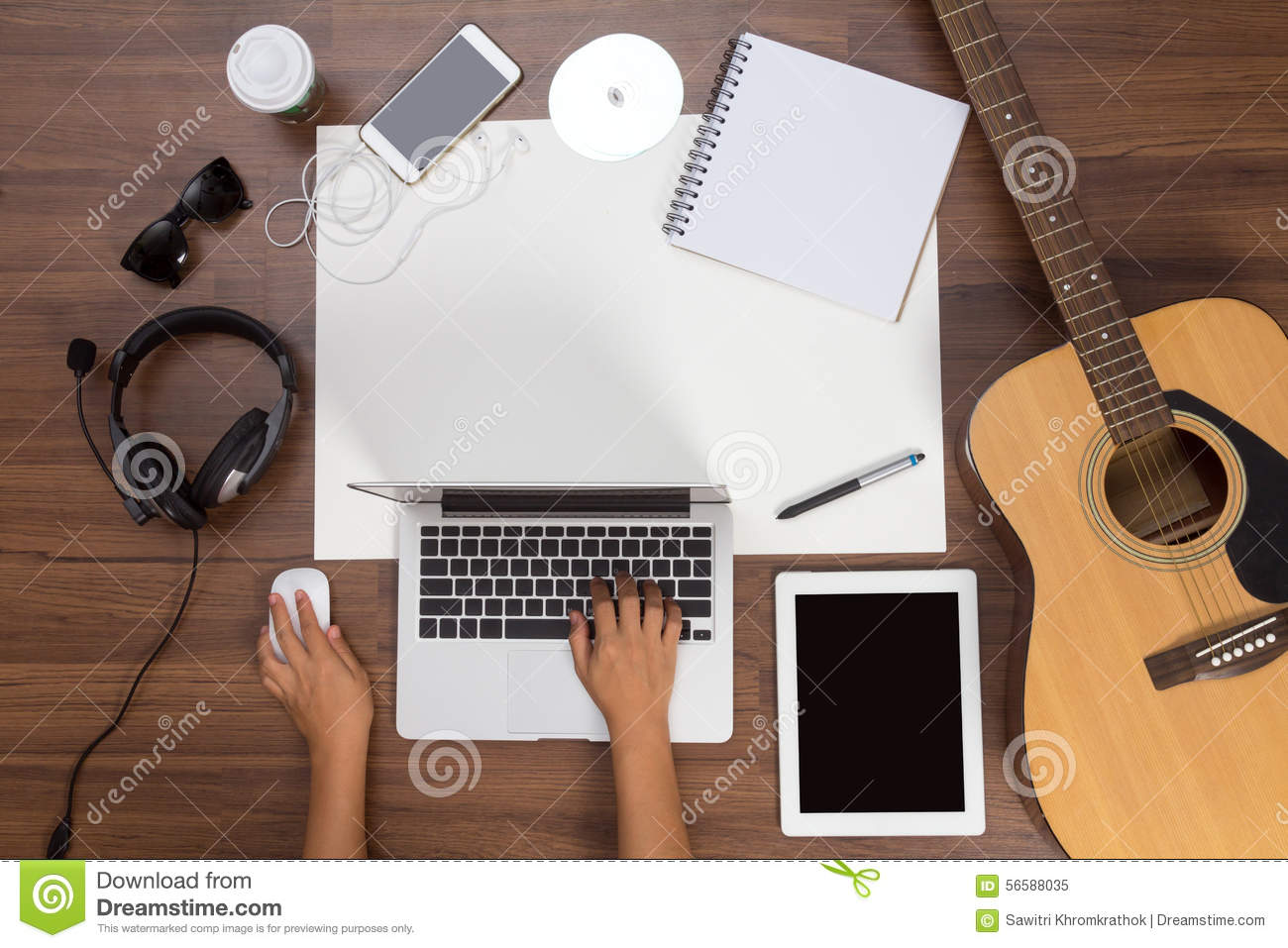 Office desk background hand using a laptop acoustic guitar and headphones
