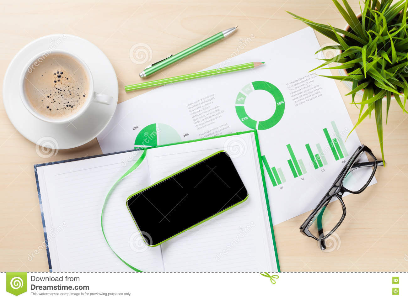 Office Desk With Charts Coffee Plant And Phone Stock