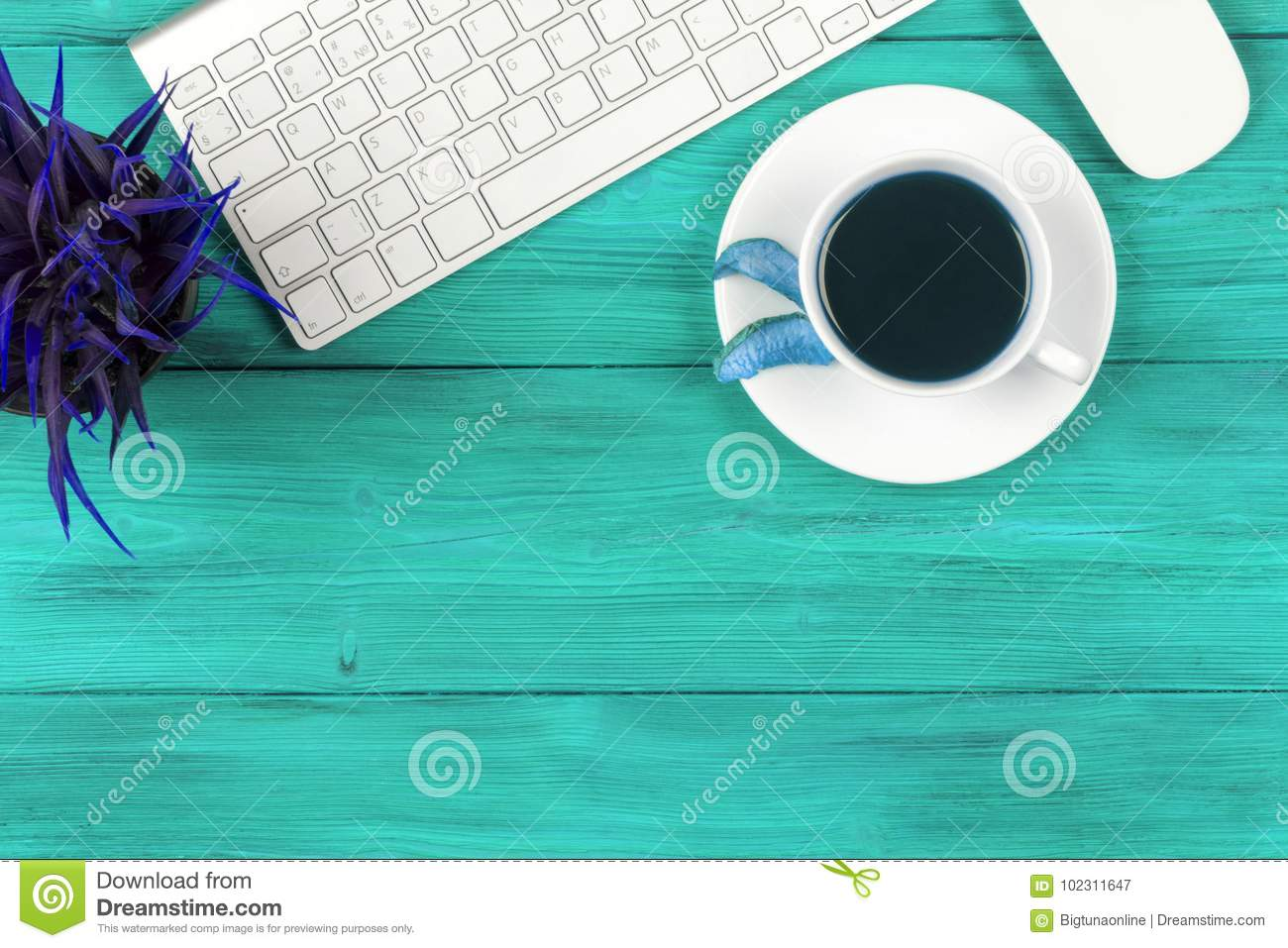Office desk with copy space. Digital devices wireless keyboard and mouse on blue wooden table with cup of fresh coffee, top view
