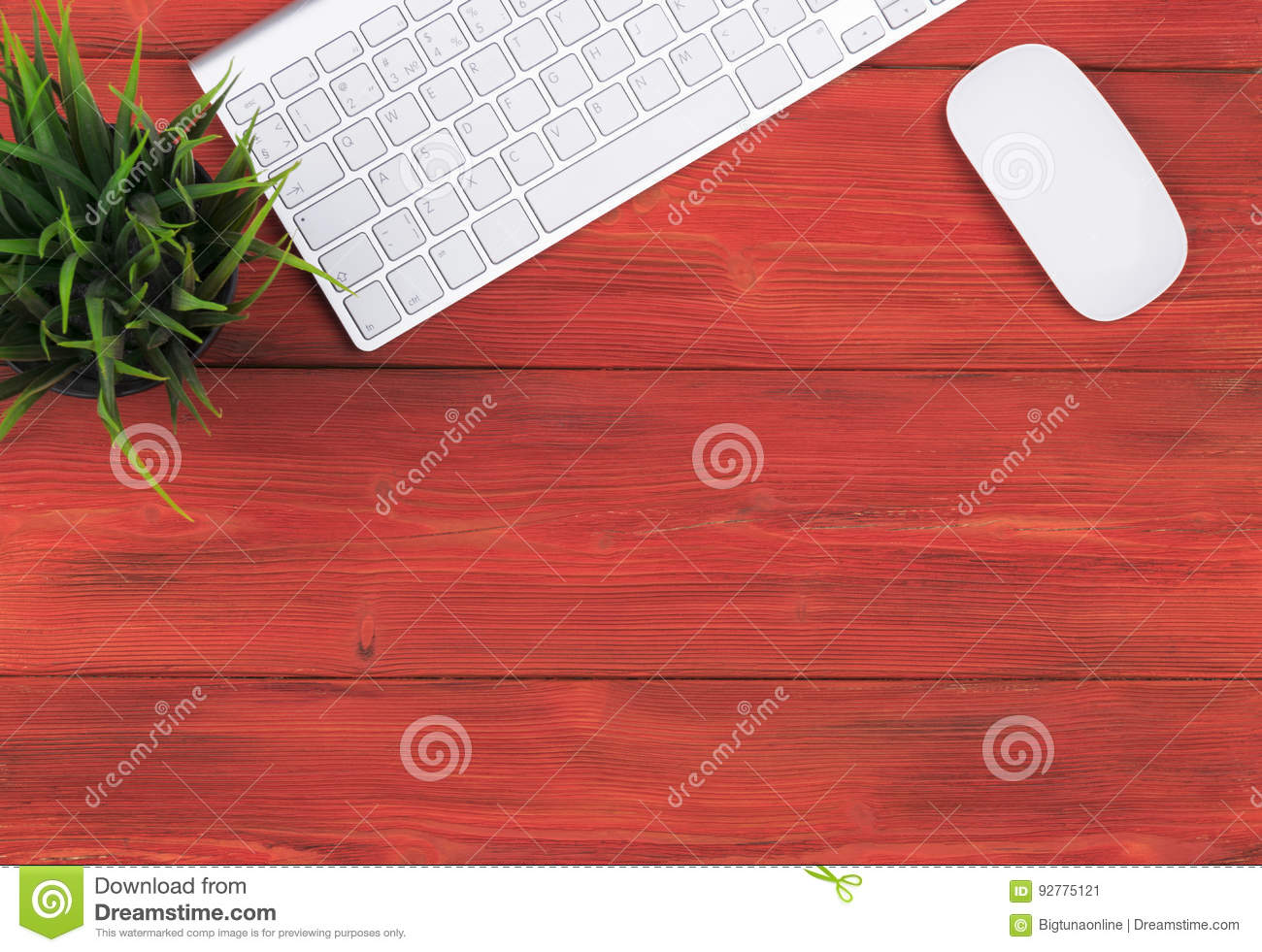 Office desk with copy space. Digital devices wireless keyboard and mouse on red wooden table, top view