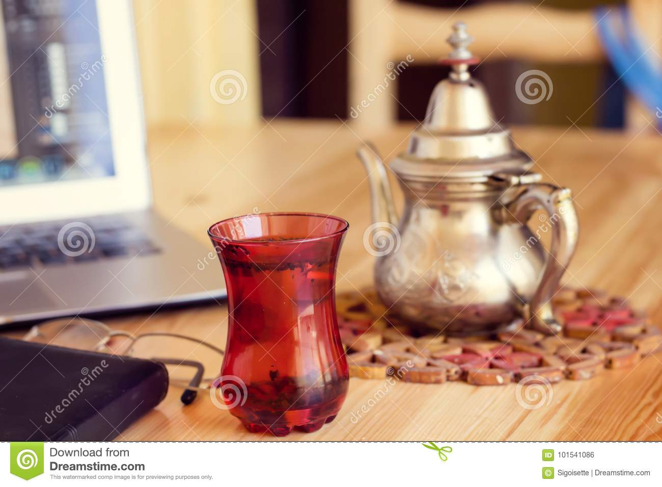 Office desk gray laptop silver arabic tea pot and notebook red cup