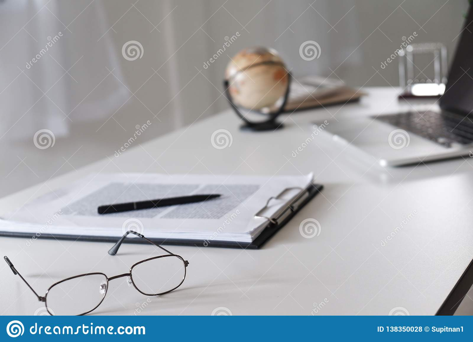 Office desk table with glasses, pen, pencil, laptop and world map
