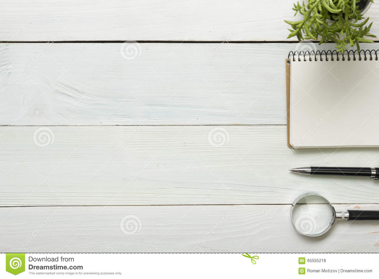 Office desk table with supplies. Top view. Copy space for text. Notepad, pen, magnifying glass, flower
