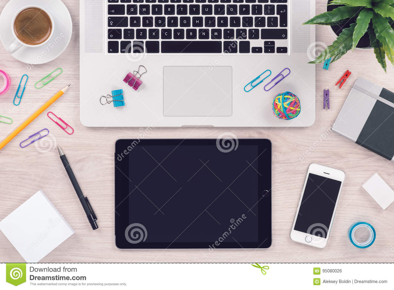 Office desk table workplace with macbook laptop keyboard, ipad tablet pc and iphone smartphone top view