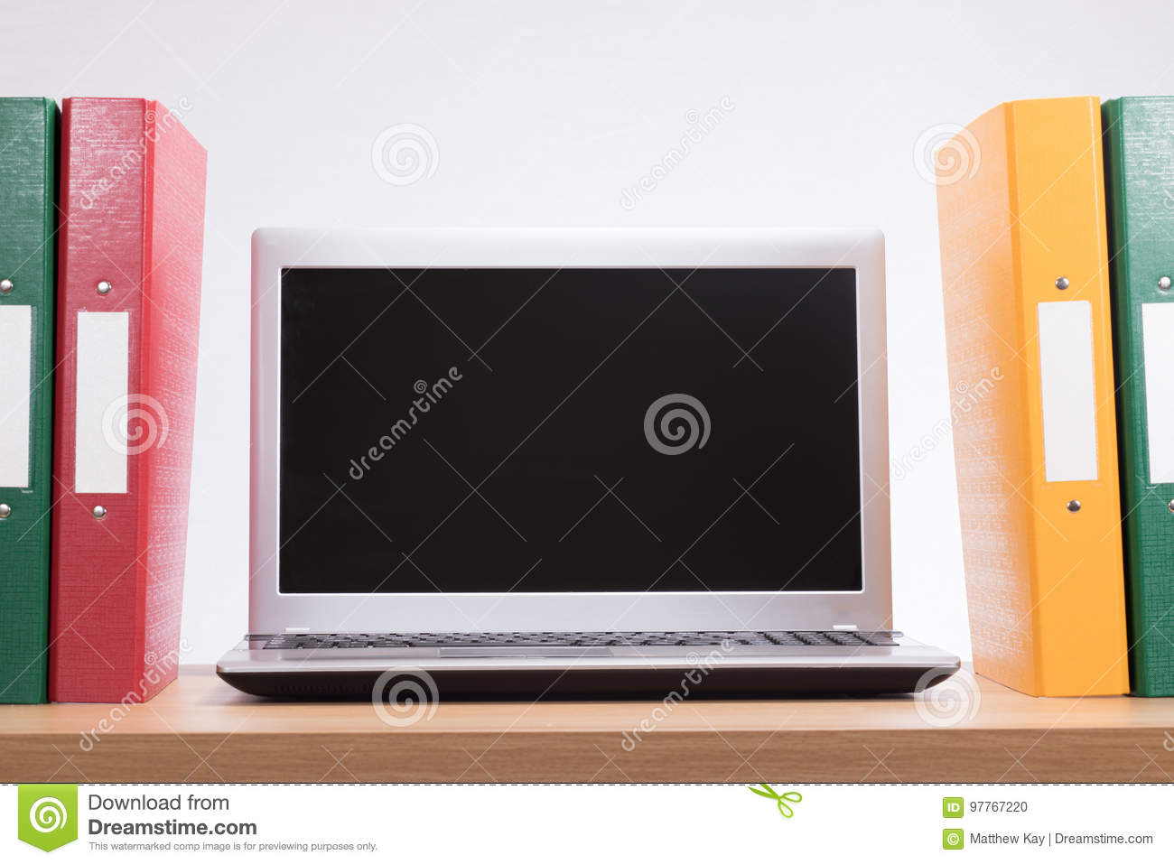 Office document folders and open laptop computer