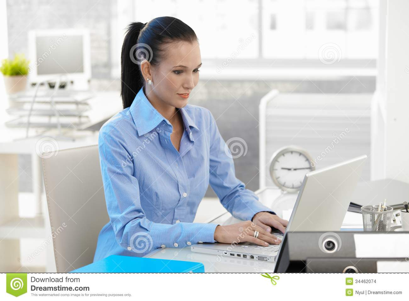 Office girl working on laptop computer at desk, looking at monitor