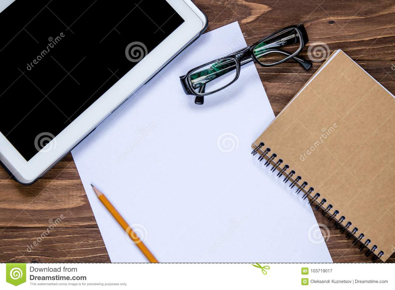 office objects set on the table examination pad and pencil glasses