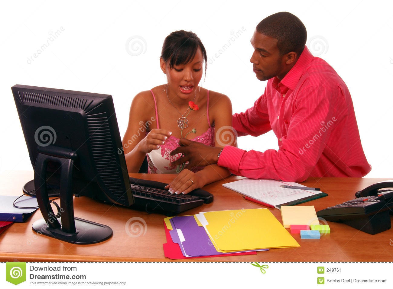 African American executive brings a flower to his secretary. Perhaps a ...