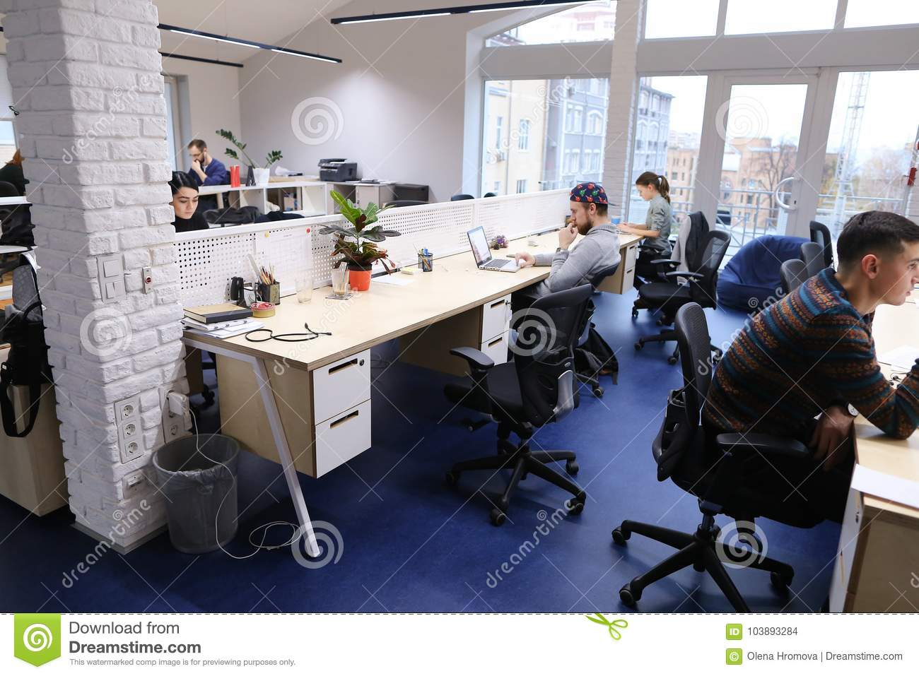 Office Space In Middle Of Working Day With People Immersed In Wo