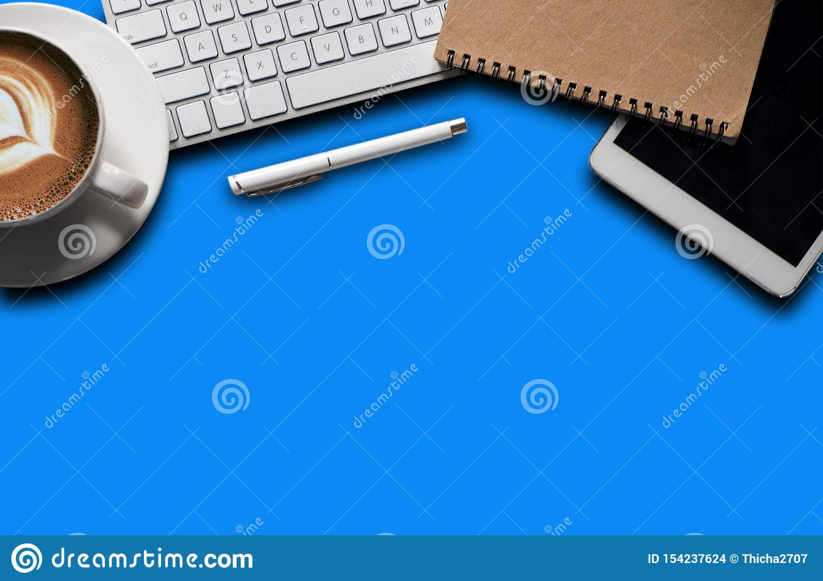 Office supplies with a laptop, smartphone, pen, tablet, notebook.