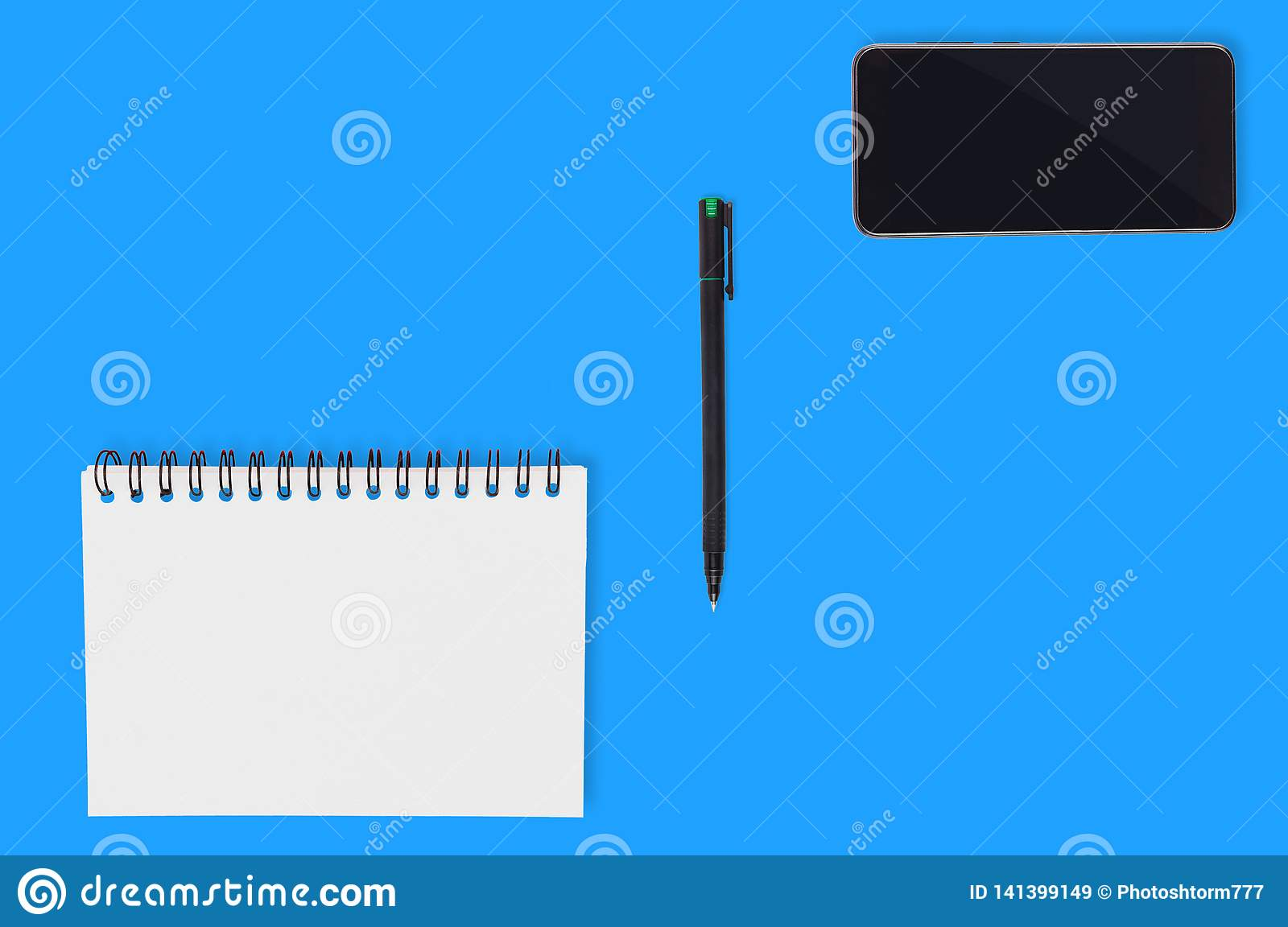 Office supplies paper notepad with blank sheet plastic pen and black smartphone spread out on blue table. Top view. Business conce