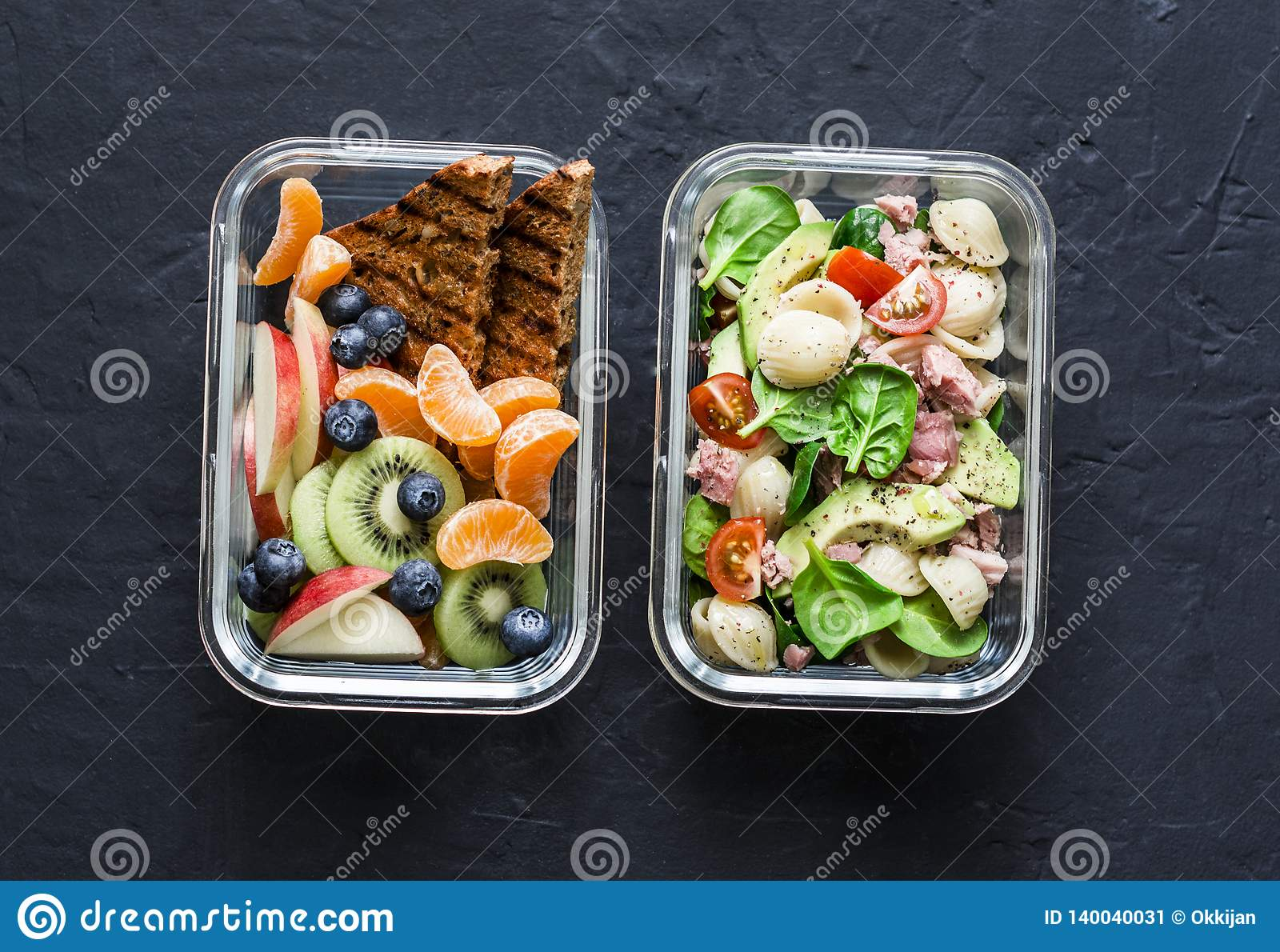 Office sweet and savory food lunch box. Pasta, tuna, spinach, avocado salad and fruit lunch box on dark