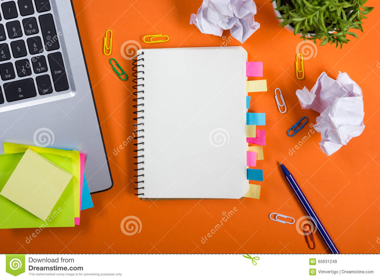 Office table desk with set of colorful supplies, white blank note pad, cup, pen, pc, crumpled paper, flower on orange
