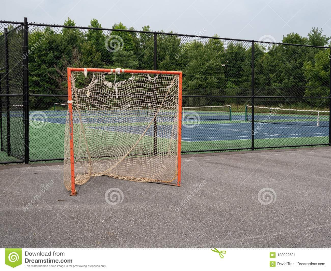 Offseason, beat up, rusted, ragged lacrosse goal sitting on asphalt court with nets tearing