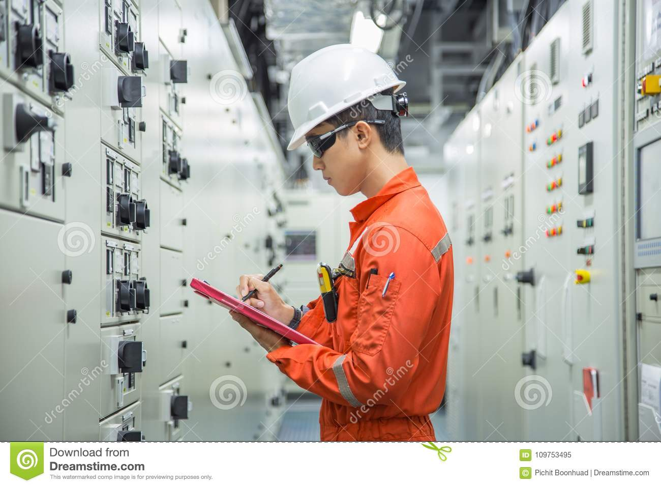Electrical and Instrument technician logging data in electrical switch gear room.