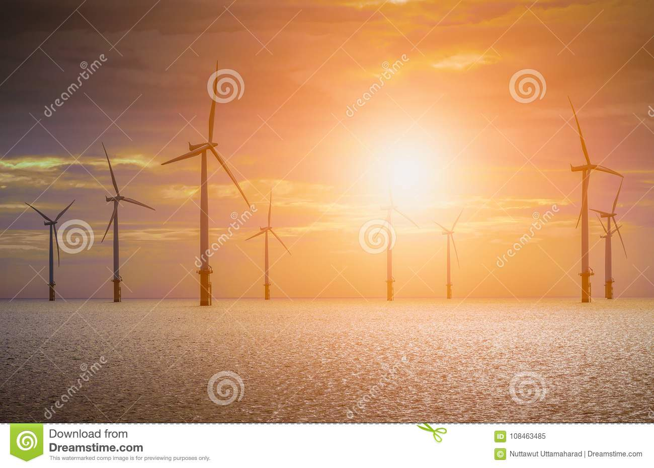 Offshore Wind Turbine in a Wind farm under construction off coast of England at sunset.