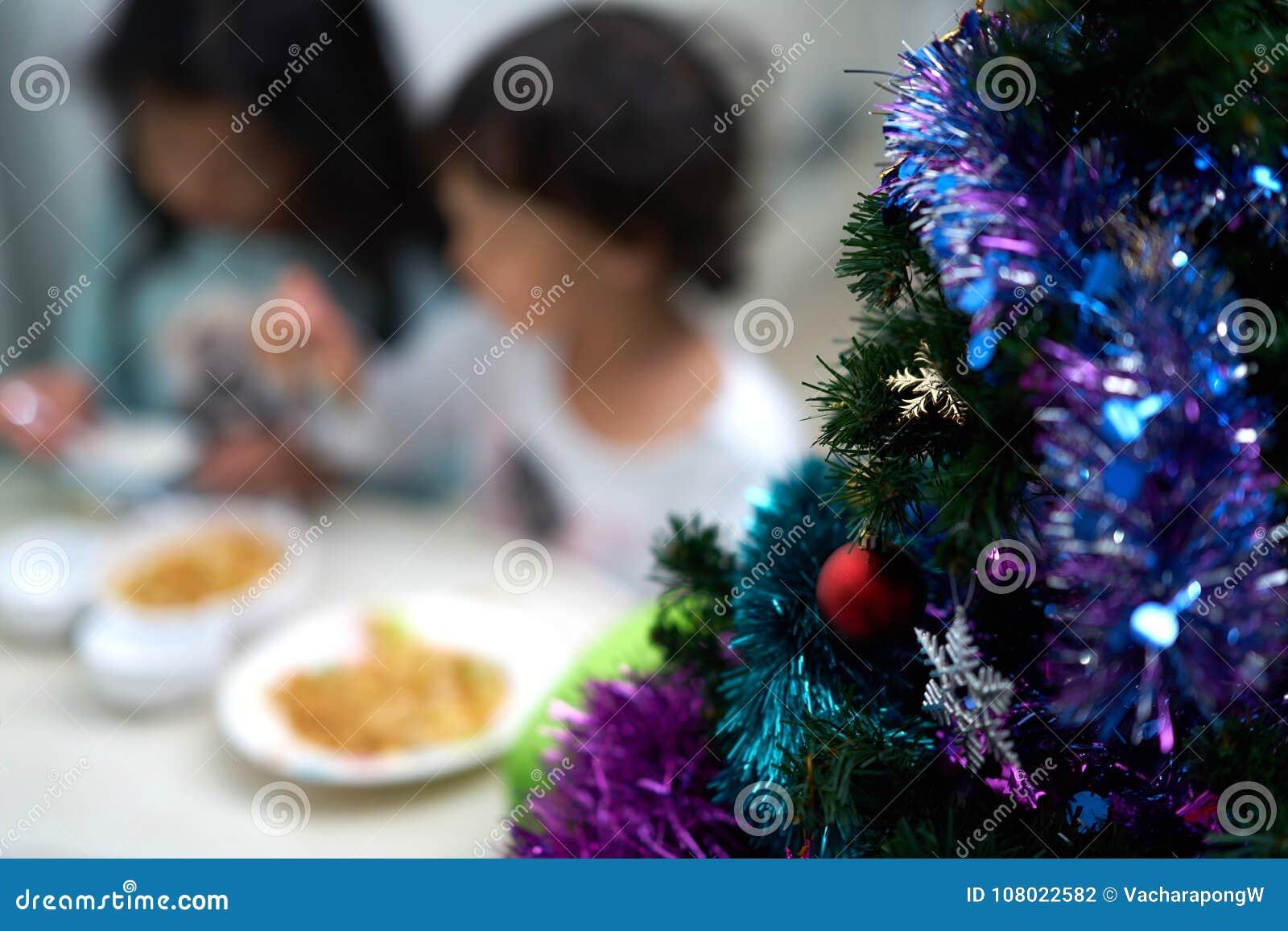 Offuschi la foto dei bambini che mangiano e goda della festa di Natale e del nuovo anno