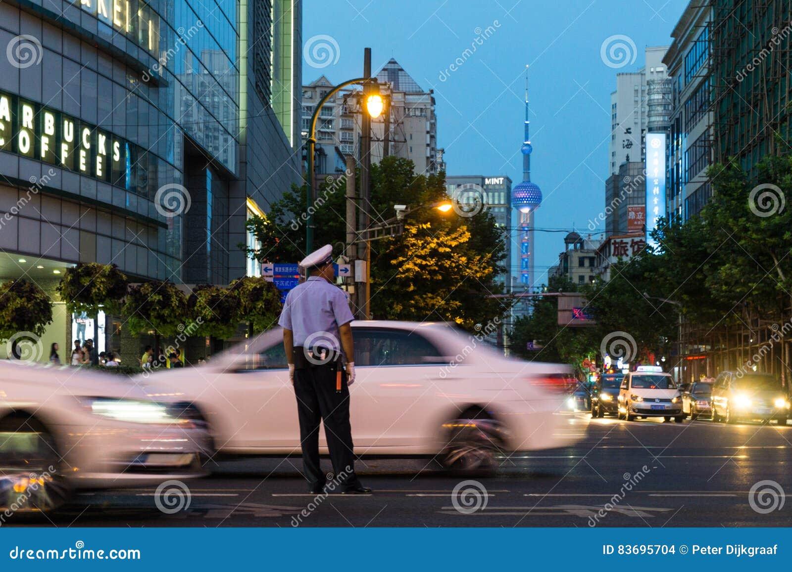 Oficial de policía que intenta controlar la locura del tráfico en Shangai Los coches están acometiendo por y en la distancia está