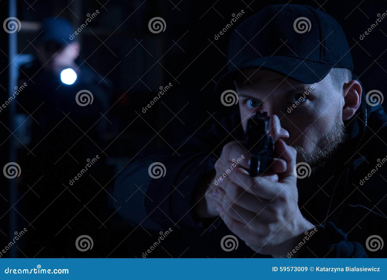 Oficial que señala el arma en el criminal