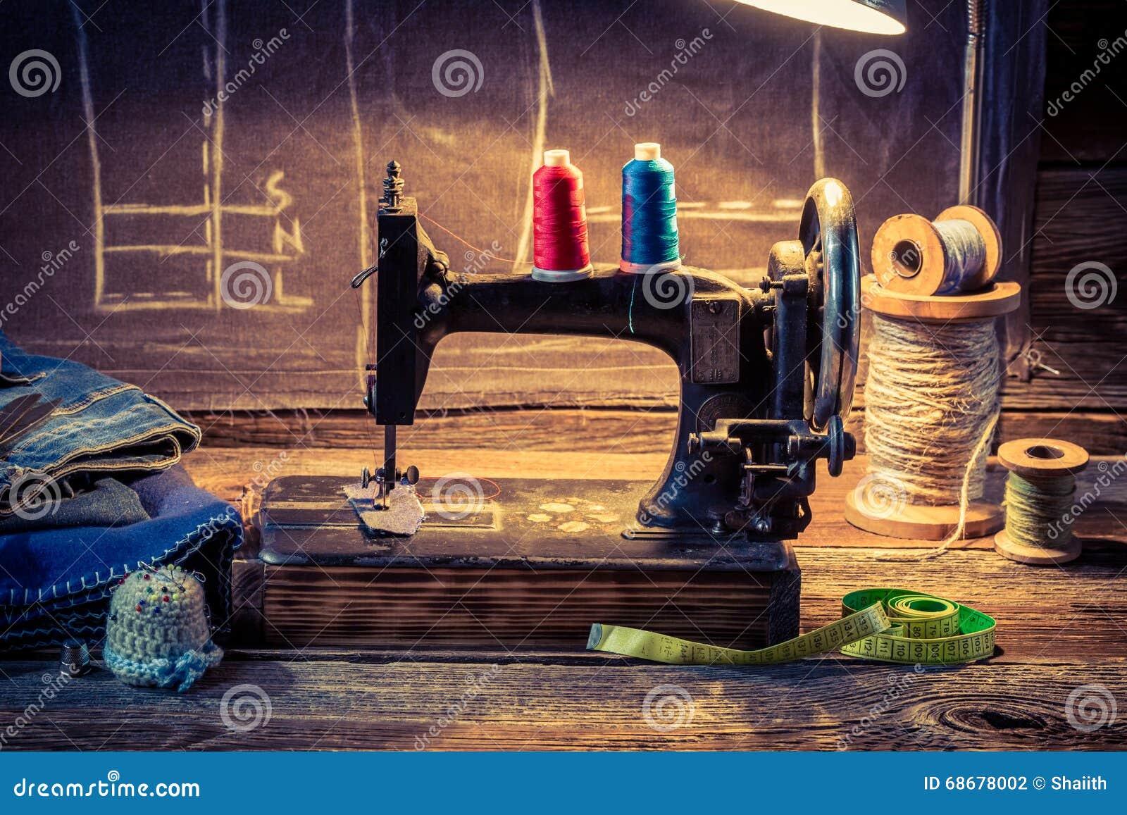 Oficina do alfaiate do vintage com máquina de costura, pano e tesouras